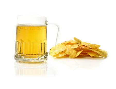 Studio macro of pint of beer and scattered potato chips (crisps) on a white surface. Copy space. photo