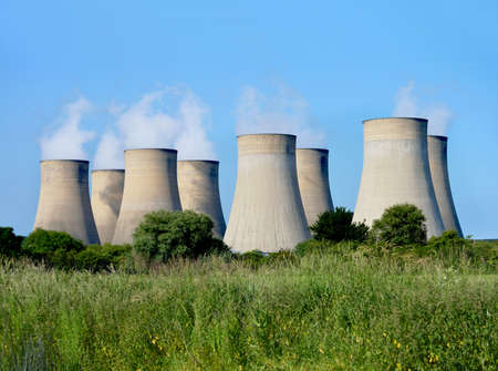 Modern power station cooling towers against a blue sky with copy space. photo