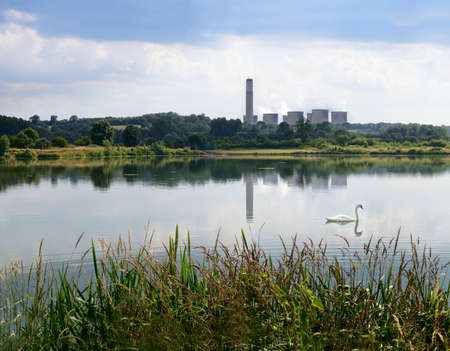 incompatible: Scenic view of the beautiful, peaceful River Trent in Nottinghamshire adjacent to Attenborough Nature Reserve  Concept image for harmony, industry and nature co-existing side by side  Copy space