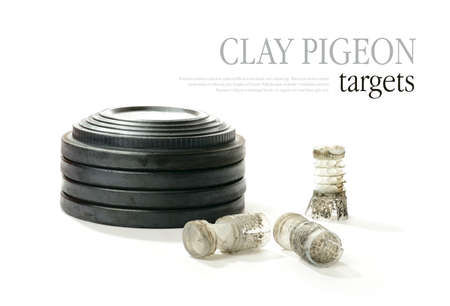 sporting activity: Studio macro of stacked clay pigeon targets and spent shotgun cartridges with soft shadows against a white background. Copy space.