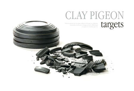 Studio macro of stacked clay pigeon targets and shattered clay with soft shadows against a white background. Copy space. Standard-Bild
