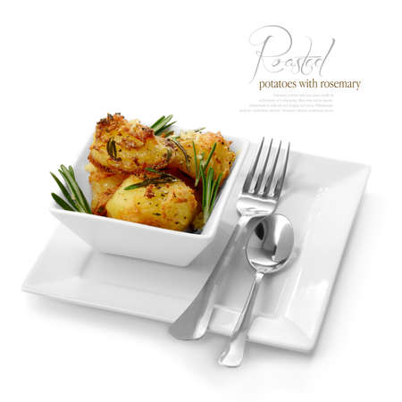 baked potatoes: Studio image of fresh seasoned roasted potatoes with black pepper, garlic and rosemary against a white background  A perfect image for your restaurant showing attention to detail  Copy space