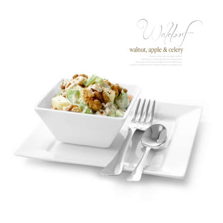 plated: Studio image of fresh Waldorf Salad with black pepper, walnuts, apple and celery against a white background  A perfect image for your restaurant showing attention to detail  Copy space