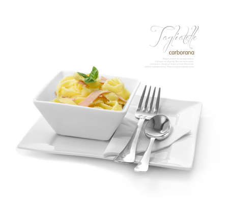 plated: Fresh Tagliatelle Carbonara with ham and grated Parmesan cheese against a white background  A perfect image for your restaurant showing attention to detail  Copy space