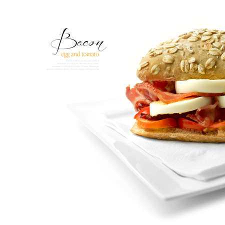 bap: Juicy, appetizing egg and bacon roll with sliced tomato against a white background with soft shadows from an interesting angle. Copy space. Stock Photo