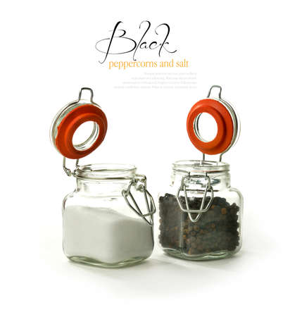 Studio image of black peppercorns and granulated salt in their respective  photo
