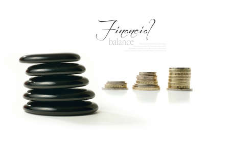 A concept image relating to financial matters  Stacked coins representing investments, pension or savings with Feng Shui black stones representing balance  White background with copy space  photo