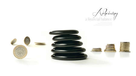 A concept image relating to financial matters  Spinning coins representing investments, pension or savings with Feng Shui black stones representing balance and the final result  White background with copy space  photo