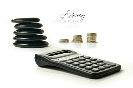 A concept image relating to financial matters  Stacked coins representing investments, pension or savings with Feng Shui black stones representing balance and a generic calculator  White background with copy space  photo
