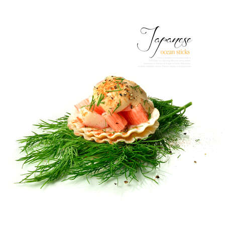Fresh Japanese crabsticks on shellfish shells with dill and seafood sauce against a white background.  photo
