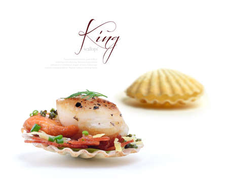 chorizo: Pan seared King Scallops in shells on a bed of grilled Chorizo, spinach leaves, lemon zest and chopped chives against isolated white A perfect image for a fish restaurant menu  Copy space  Stock Photo