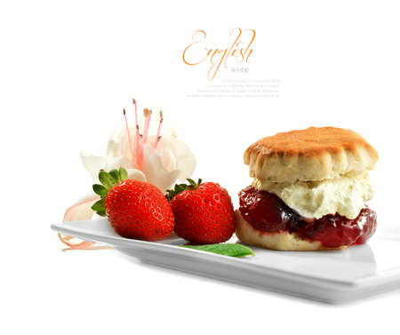 A fully loaded freshly-made English scone oozing with double whipped  cream and strawberry jelly against isolated white The perfect image for a cafe menu or summer party invitation  Copy space  photo