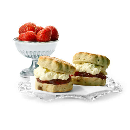 Two freshly-made English scone oozing with double whipped  cream and strawberry jelly against a isolated white . The perfect image for a cafe menu or summer party invitation. Copy space. Banque d'images
