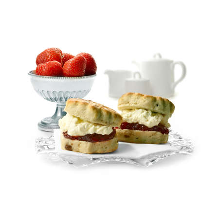 Two freshly-made English scone oozing with double whipped  cream and strawberry jelly against a isolated white . The perfect image for a cafe menu or summer party invitation. Copy space. Standard-Bild
