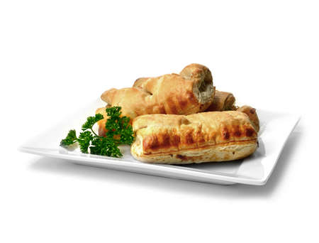 calories poor: Three freshly baked sausage rolls with a garnish against a white background  Copy space