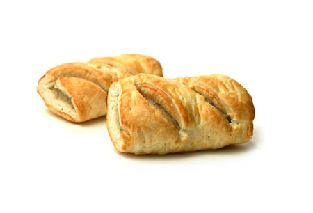 calories poor: Two freshly backed sausage rolls with soft shadows against a white background  Copy space