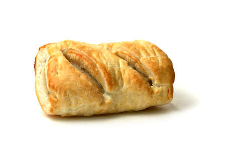 calories poor: Single freshly backed sausage roll with soft shadows against a white background  Copy space  Stock Photo