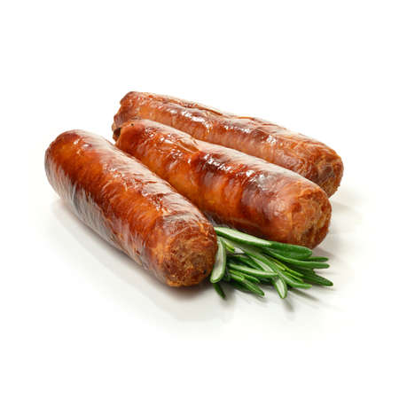 Studio close up of pin sharp focus grilled pork sausages stacked against a white surface with rosemary sprigs and soft shadows  Copy space