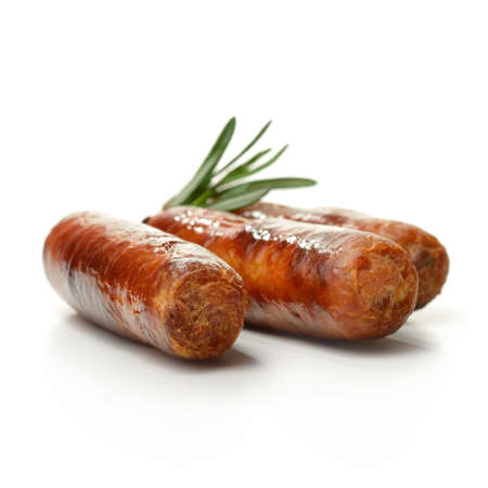 british food: Studio close up with shallow focus grilled pork sausages stacked against a white surface with rosemary sprigs and soft shadows  Copy space  Stock Photo