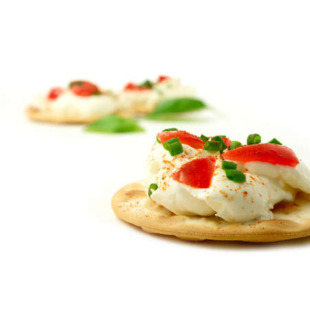 Sharply focused macro of fresh cream cheese and tomato canape against a white background. Standard-Bild