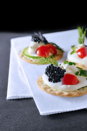 selectively: Selectively light studio image of caviar canapes on a white napkin. Copy space. Stock Photo