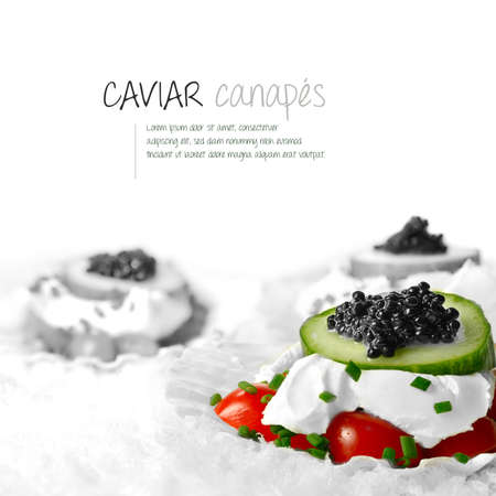 Freshly prepared black caviar and soft cheese canapes styled on scallop shell in snow.  photo