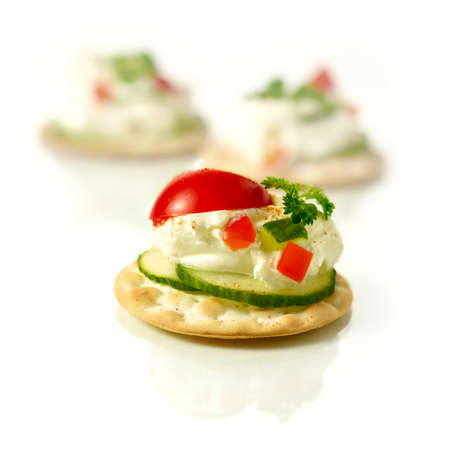 Delicious freshly prepared cream cheese canapes with cucumber, chilli peppers and tomatoes with a parsley garnish against a white background. Copy space. photo