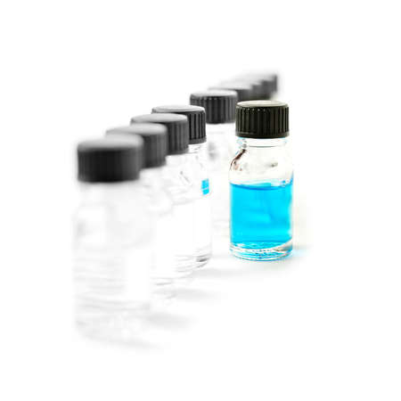 research and development: High-key studio macro of laboratory specimen bottles filled with clear liquid with one filled with blue against a white background  Copy space