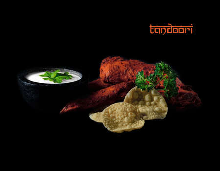 Indian mini poppadums with Tandoori chicken fillets with mint raita and garnish against a black background  Creative studio lighting  Copy space