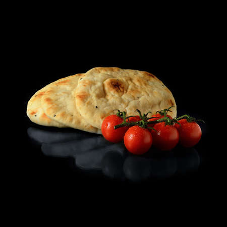 Stacked, warm Indian naan breads with dew covered tomatoes against a black background with soft reflections  Copy space photo