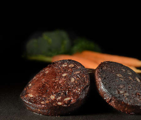 Traditionally English black pudding slices on polished slate  Copy space