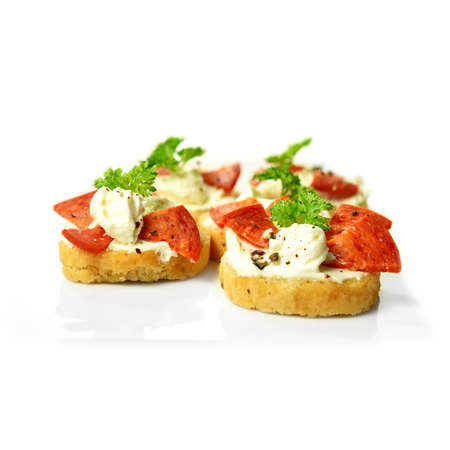 Freshly made cream cheese and pepperoni bruschetta with a parsley garnish against a white background