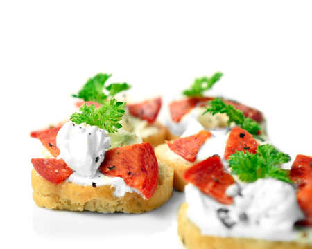 Freshly made cream cheese and pepperoni bruschetta with a parsley garnish against a white background photo