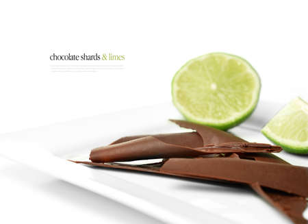 shards: Dark shards of chocolate with fresh cut limes against a white background. Copy space. Stock Photo
