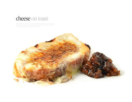 Cheese on toast also known as Welsh Rarebit - Toasted bread with melted cheddar cheese, drizzled Worcester sauce and a rich pickle, chutney relish. Copy space.