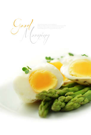 asparagus bed: Stylishly studio lit image of soft poached eggs with steamed asparagus stems against a bright background. Perfect for your breakfast menu design or healthy eating articles. Copy space.