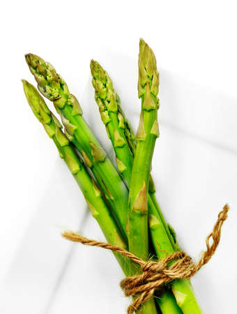 overhead shot: Close-up of fresh asparagus stems tied with old twine lying on a  white plate. Overhead shot. Copy space.