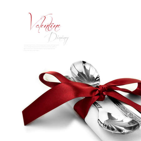 Concept image for Valentine dining or wedding breakfast.Two antique silver spoons on a pure white linen napkin with a burgundy red tie and bow against a white background. Copy space.