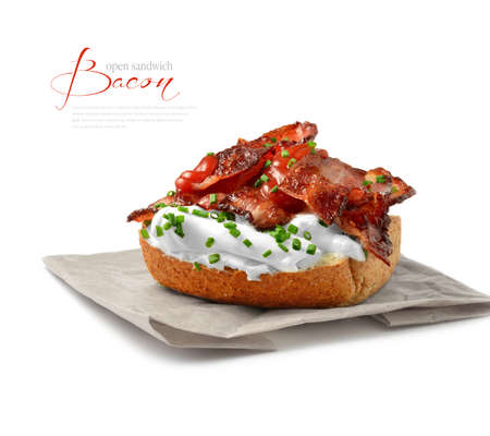 The ultimate open bacon sandwich. A slab of wholemeal bread topped with a generous serving of soft cream cheese smothered in layers of sizzling  bacon rashers with tomato sauce relish. Copy space.