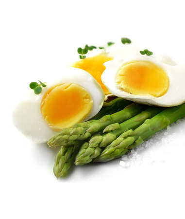 Close-up image of soft poached eggs with steamed asparagus stems and rock salt granules against a bright background. Perfect for your breakfast menu design or article on healthy eating. Copy space.