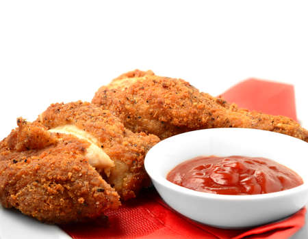 Close up of freshly cooked Southern Fried Chicken pieces with tomato ketchup side order against a white background  Copy space  photo