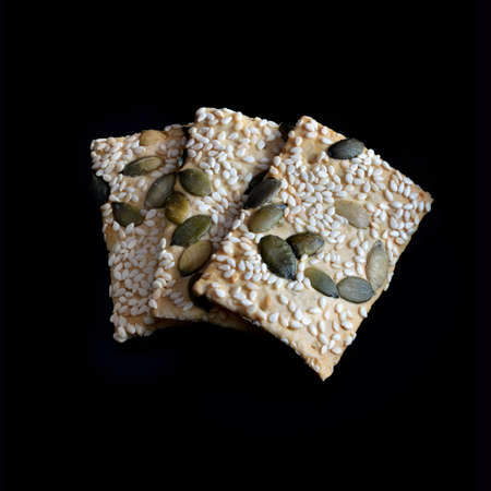 Sesame And Pumpkin Seed Flatbreads in natural light against black  Copy space  photo