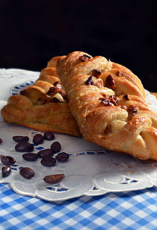 Freshly made maple and pecan plait Danish pastry on a blue napkin with serviettes. The perfect image for your bistro or cafe designs. Copy space. photo