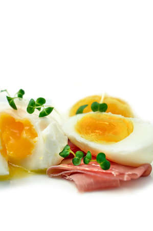 Macro of freshly prepared poached eggs with prosciutto, Italian ham, with sprigs of garden cress as a garnish. Copy space. photo