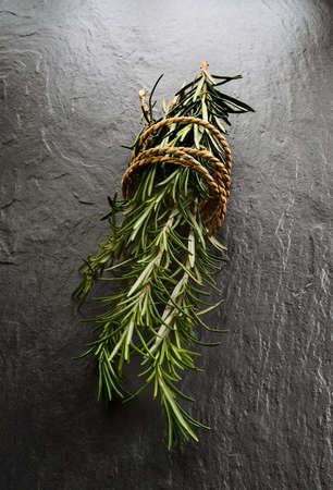 rosemary flower: Fresh Rosemary - Rosmarinus officinalis - tied with string on grey slate  Shot in mystic light style  Copy space