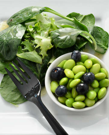 Overhead shot of super food salad  Edamame beans with blueberries and green leaf salad  Copy space  Stock Photo