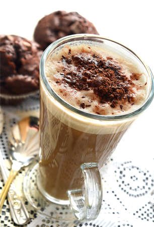 Overhead shot of fresh Cappuccino coffee with chocolate sprinkles accompanied with triple chocolate muffins and silver spoons
