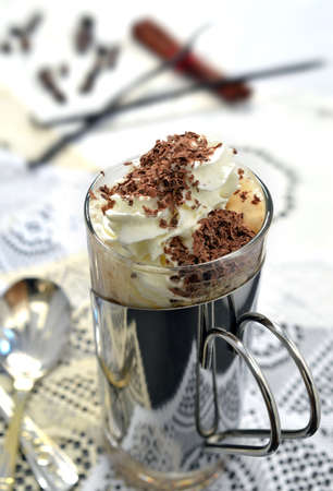 capucinno: Fresh cappuccino coffee with whipped cream and chocolate sprinkles  Coffee beans, cinnamon and vanilla pods blurred in the background  Copy space