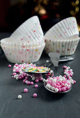 Pink and white cake decorations with empty cup cake cases in background  Shallow depth of field  Copy space  photo