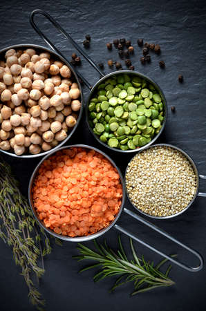 Overhead shot of pulses, chickpeas, lentils, Quinoa and black peppercorns against a stone surface with fresh herbs  Concept image for healthy or vegetarian cooking